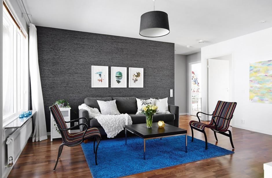 Dominujące w salonie szarości przełamano jednym, intensywnym akcentem kolorystycznym. Na podłodze leży kosmaty dywan o pięknej barwie głębokiego indygo. Fot. Vastanhem.