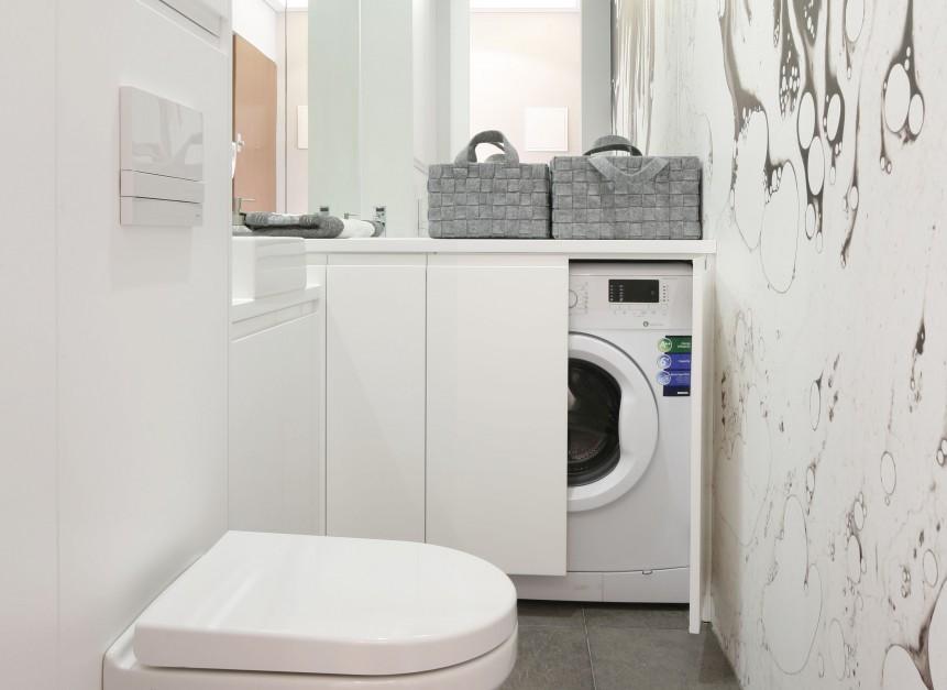 Mała łazienka została tak praktycznie i pomysłowo zaprojektowana, że zmieściła się tutaj nawet pralka ukryta w zabudowie. Projekt: Karolina Łuczyńska. Fot. Bartosz Jarosz.