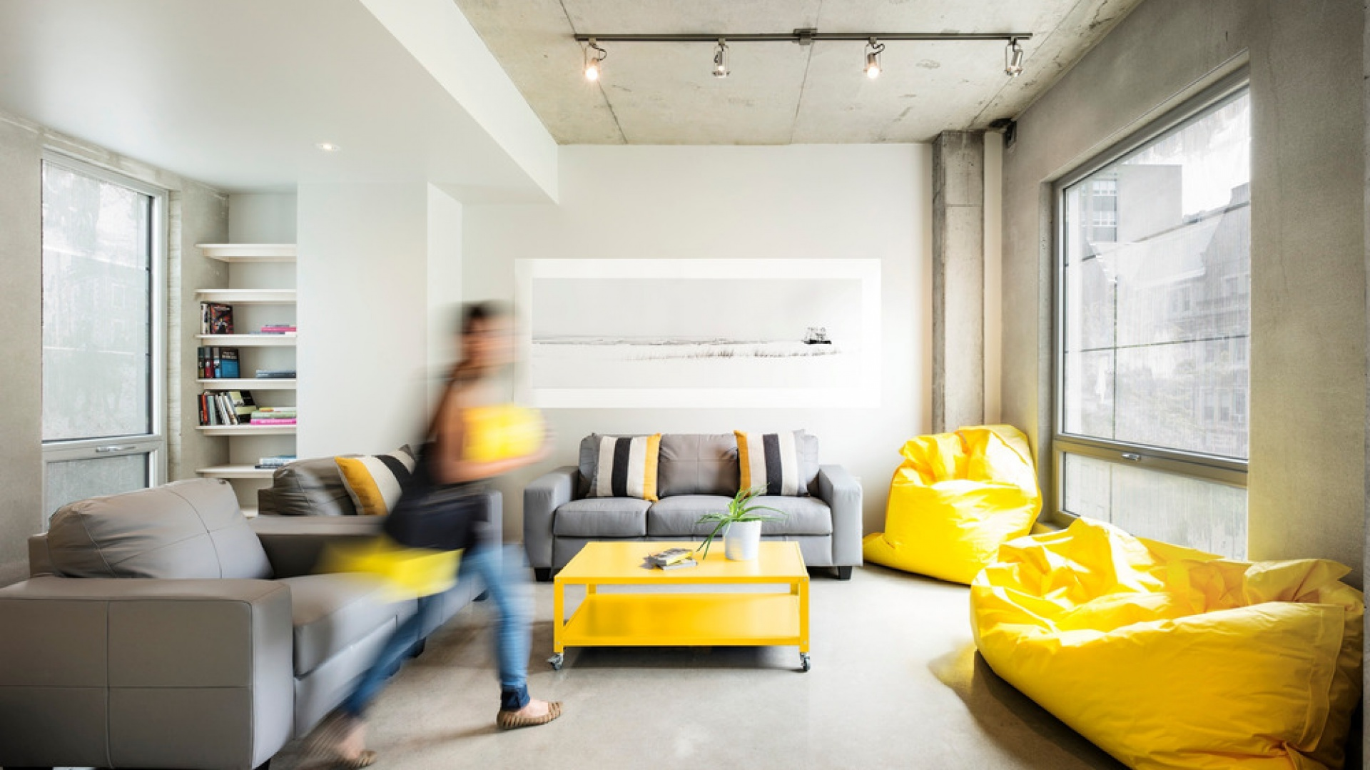 Pomiędzy fasadami budynku, a jego wnętrzem zachowano niczym niezmąconą harmonię. W salonie również dominującym materiałem jest beton. Korespondują z nim szare meble wypoczynkowe, a żółte elementy ożywiają aranżację. Projekt: KANVA. Fot. Marc Cramer.