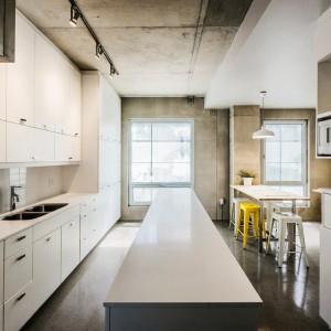 W centrum kuchni stoi długa, obszerna wyspa, sprzyjająca wspólnemu pichceniu. Białe meble wykończone na wysoki połysk rozświetlają betonową przestrzeń. Projekt: KANVA. Fot. Marc Cramer.