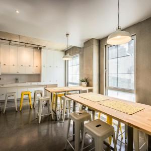 W kuchni panuje delikatnie industrialny klimat - nad stołami zwisają loftowe lampy, a przy stołach ustawiono metalowe stołki. Projekt: KANVA. Fot. Marc Cramer.