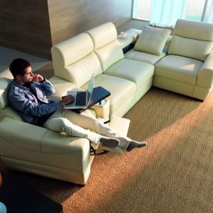 Grand Vario to modułowa sofa z funkcją relaksu, wyposażana w podwyższone oparcia, z możliwością regulacji stopnia ich nachylenia, wysuwany podnóżek fotela oraz szerokie podłokietniki. Niezwykle użytecznym elementem mebli są dostępne opcjonalnie w elemencie narożnym praktyczne półki a także ruchoma półka, idealna do pracy z laptopem. Fot. Etap Sofa.