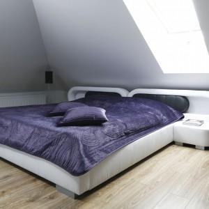 Z uwagi na duży spadek ścian, wybrano łóżko z niskim wezgłowiem, które jednocześnie pełni rolę szafek nocnych. Tuż przy nich ustawiono niewysokie lampy podłogowe w minimalistycznym stylu. Projekt: Marta Kilan. Fot. Bartosz Jarosz.