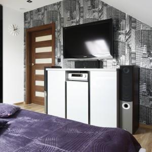 Ścianę bez skosów wykorzystano do powieszenia na niej telewizora. Aby podkreślić nowoczesny charakter aranżacji wykończono ją minimalistyczną tapetą z motywem wieżowców. Projekt: Marta Kilan. Fot. Bartosz Jarosz.