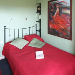 W dość wąskim pomieszczeniu króluje modny kontrast czerwieni z jasną zielenią. Aby uzyskać przestrzeń komunikacyjną kute łóżko ustawiono tuż przy ścianie. Projekt: Marta Kruk. Fot. Bartosz Jarosz.