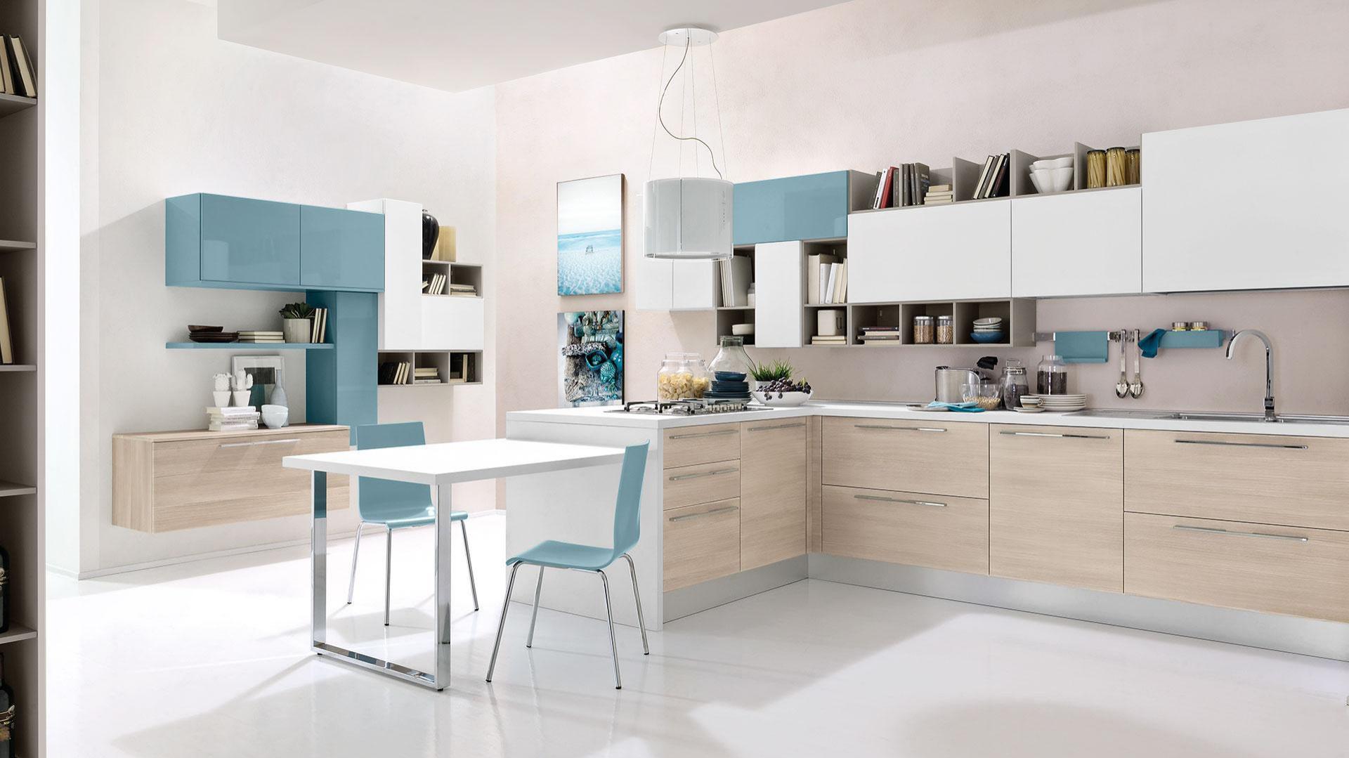 Delikatne, harmonizujące ze sobą barwy: kolor jasnego drewna, niczym niezmącona biel i błękit w wysokim połysku. Subtelne kolory mebli i asymetryczne kształty czynią z tej kuchni kobiecą, nowoczesną aranżację, a półwysep przedłużony o blat, pełniący funkcję stołu jest funkcjonalnym dodatkiem. Fot. Cucine Lube, model Swing.