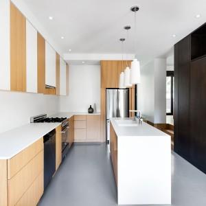 Nowoczesna kuchnia z wyspą, w obrębie której zlokalizowano zlewozmywak. Fronty mebli górnej zabudowy kuchennej układają się w naprzemienny wzór: kolor drewna i przełamana, gładka biel. Projekt: Nature Humaine. Fot. Adrien Williams.