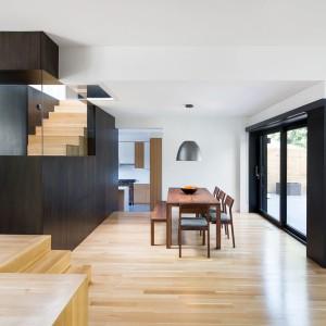 Jadalnię położono pomiędzy dwoma salonami a kuchnią, w ciągu komunikacyjnym, wyznaczonym przez centralny rdzeń architektoniczny przestrzeni domu. Po drugiej stronie zamykają ją panoramiczne przeszklenia, wpuszczając naturalne światło dzienne do środka jadalni. Spożywane tutaj posiłki smakują szczególnie wybornie Projekt: Nature Humaine. Fot. Adrien Williams.