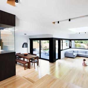 Wystrój wnętrza domu jest nowoczesny i bardzo oszczędny, wręcz minimalistyczny. Mimo wszystko w środku jest przytulnie, dzięki bogato zastosowanemu drewnu, w jasnych i ciemnych odcieniach. Projekt: Nature Humaine. Fot. Adrien Williams.