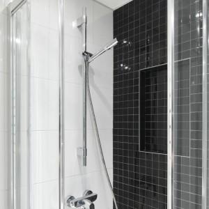 Pod prysznicem zdecydowano się na połączenie dwóch kontrastujących płaszczyzn. Duże, białe płytki kontrastują z czarnymi, na których jest widoczny geometryczny podział.  Fot. Bartosz Jarosz.