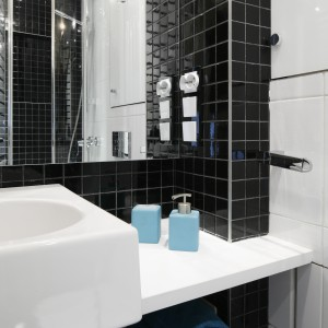 Biało-czarna łazienka stanowi doskonałe tło dla dodatków w każdym kolorze. Kolorowe dozowniki, ręczniki ożywiają wnętrze łazienki. Fot. Bartosz Jarosz.