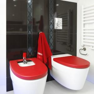 Czerwone deski na sedesie i bidecie sprawiają, że zwykła ceramika zyskuje oryginalny wygląd, a całe wnętrze - niepowtarzalny styl. Projekt: Marta Kilan. Fot. Bartosz Jarosz.