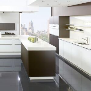 Nowoczesna kuchnia, w której ciepły kolor ciemnego brązu zestawiono z kontrastującą bielą. Grubość blatu została dodatkowo wyeksponowana przez kontrastujący z bielą ciemny brąz. Fot. Brigitte Kuechen, model Topas.
