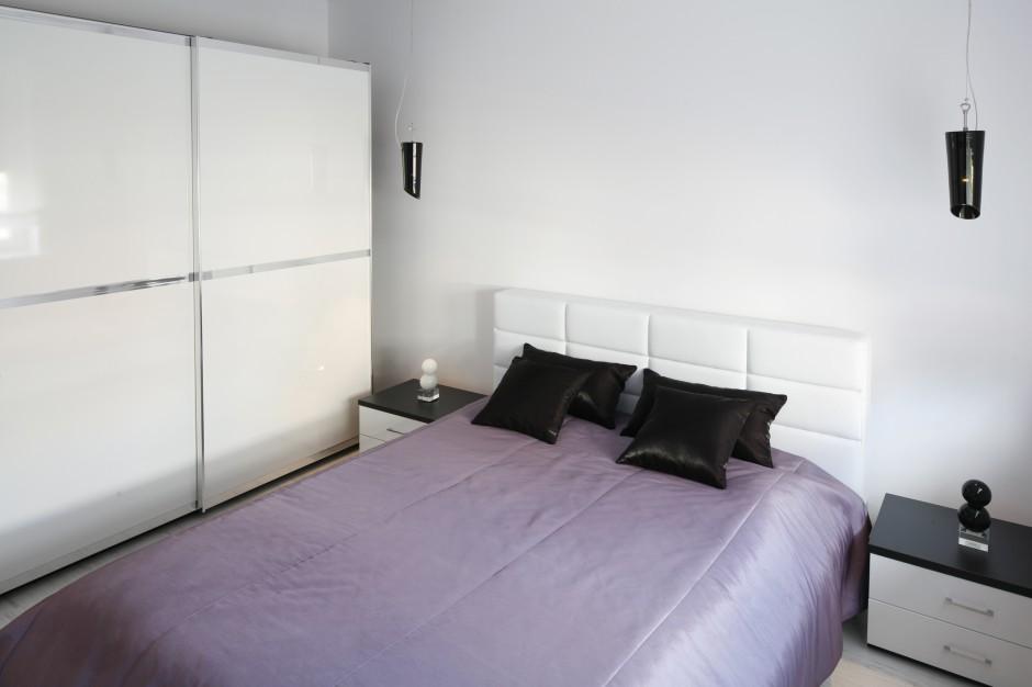 Białą szafę z drzwiami przesuwnymi ustawiono równolegle do łóżka. Stalowe elementy na drzwiach sprawiają, że mebel nawiązuje wyglądem do pikowanego zagłówka, podkreślając nowoczesny styl aranżacji. Projekt: Joanna Ochota. Fot. Bartosz Jarosz.