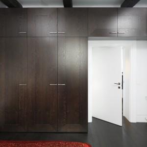 W tej sypialni wolną przestrzeń wykorzystano do maksimum. Zabudowa w kolorze ciemnego drewna, kontrastującym z bielą ścian, zajmuje całą powierzchnię ściany, zarówno obok drzwi jak i nad nimi. Projekt: Iza Mildner. Fot. Bartosz Jarosz.