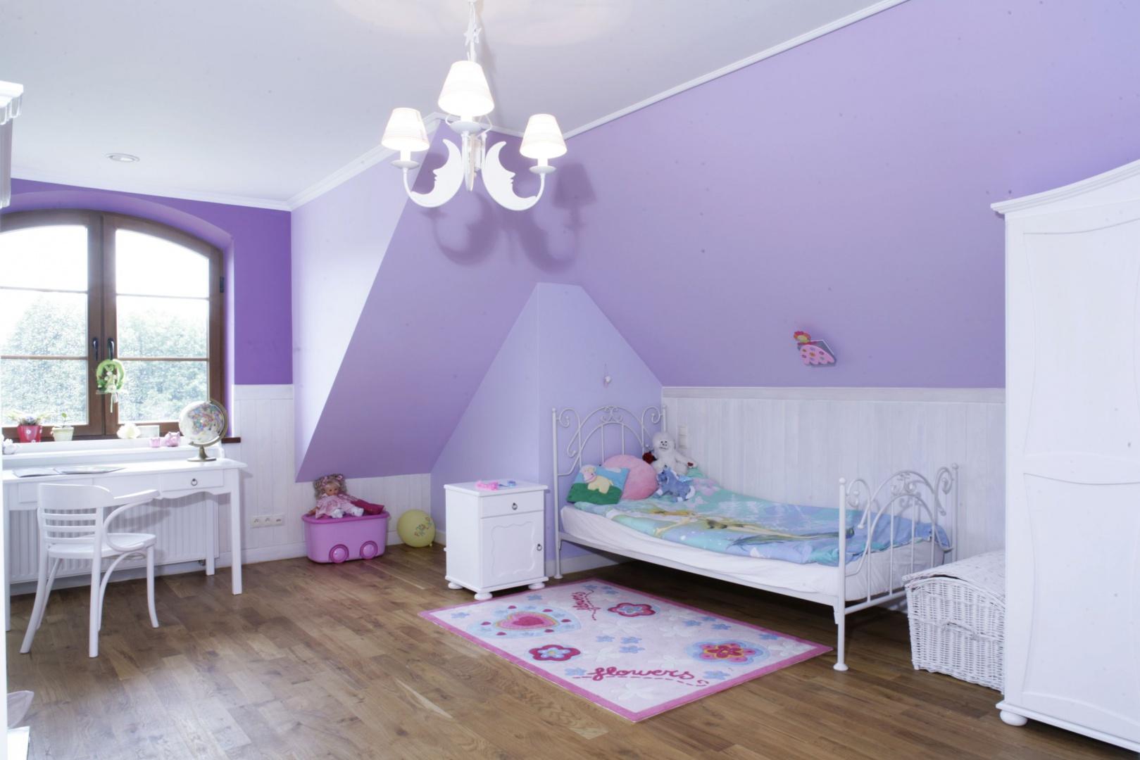 W przestronnym wnętrzu panuje połączenie lekkiego, jasnego fioletu oraz bieli. Ściany wyłożono białą boazerią natomiast skosy pomalowano na liliowo, co nadało pomieszczeniu dziewczęcy, romantyczny wygląd. Fot. Bartosz Jarosz.