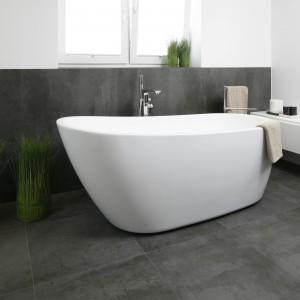Wolno stojąca wanna stanowi najważniejszy element wyposażenia łazienki. Ciekawą formę wanny podkreślają szare, wielkoformatowe płytki znajdujące się na ścianie i podłodze. Fot. Bartosz Jarosz.