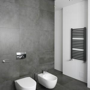 Biel i szarość przełamują czarne akcenty. Na białej ścianie umieszczono czarny, kontrastujący grzejnik drabinkowy. Fot. Bartosz Jarosz.