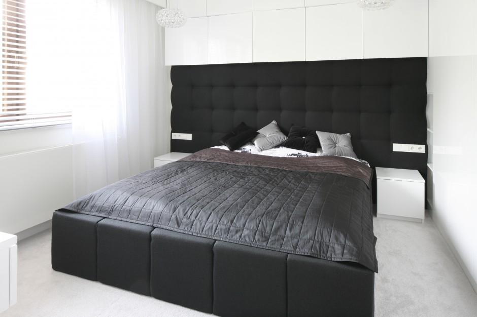 Nowoczesne, eleganckie łóżko ustawiono na środku sypialni. Rolę zagłówka pełni pikowana ściana, do połowy tapicerowana czarną, miękką tkaniną. Fot. Bartosz Jarosz.