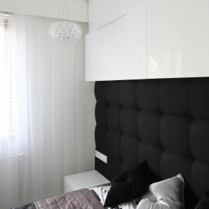 Górną część ściany nad łóżkiem zagospodarowano pod minimalistyczną zabudowę. Białe fronty lakierowane na wysoki połysk podkreślają nowoczesny charakter aranżacji. Fot. Bartosz Jarosz.