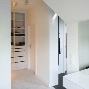 Elementem łączącym przestrzeń sypialni i garderoby jest jasnoszara, jednolita wykładzina, wyłożona na podłodze w obu pomieszczeniach. Fot. Bartosz Jarosz.