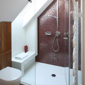 Strefę prysznica wydzielono dość nietypowo, bo pod oknem dachowym. Ścianę z panelem prysznicowym obłożono mieniącą się mozaiką, która stanowi ciekawą dekorację wnętrza. Projekt: Magdalena Konopka, Maciej Konopka. Fot. Bartosz Jarosz.