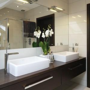 Ciemnobrązowe szafki pod umywalką świetnie kontrastują z jasnymi ścianami. Duże lustro optycznie powiększa wąską łazienkę. Projekt: Magdalena Biały. Fot. Bartosz Jarosz.