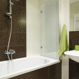W tej niewielkiej łazience postawiono na jasnobeżowe i brązowe płytki ceramiczne na ścianach z takim samym delikatnym wzorem. Na uwagę zasługuje parawan wannowy, który po rozłożeniu pełni funkcję wygodnej zasłony prysznicowej. Projekt: Marta Kilan. Fot. Bartosz Jarosz.