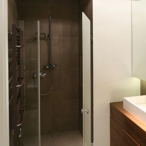 Dokładnie tak została zaaranżowana ta łazienka: biała ściana i jaśniejsza podłoga idealnie kontrastują z brązowymi płytkami, którymi wyłożono także ściany pod prysznicem. Projekt: Agnieszka Ludwinowska. Fot. Bartosz Jarosz.