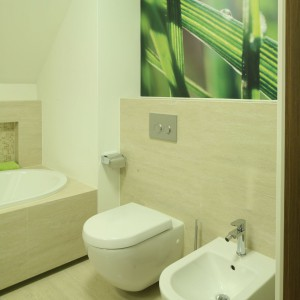 W tej łazience wyraźnie widać inspiracje naturą, na co wskazuje dobór materiałów i kolorów. Trawertyn i drewno uzupełnia motyw roślinny na fototapecie.  Projekt: Magdalena i Marcin Konopka. Fot. Bartosz Jarosz.