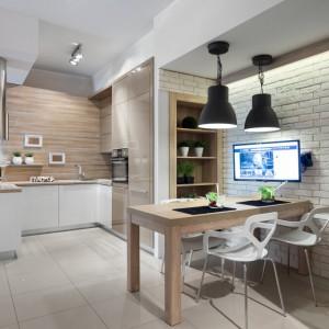 Piękna kuchnia w kolorze kawy z mlekiem. Mały półwysep jest centrum gotowania oraz elementem działowym, odgraniczającym kuchnię od reszty wnętrza. Blat półwyspu kolorem harmonizuje z cegłą na ścianie i dekorem drewnianym nad blatem. Fot. Pracownia Mebli Vigo.