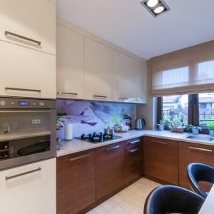 Beżowo-brązową aranżację kuchni urozmaica ściana nad blatem, ozdobiona fototapetą z eterycznym motywem w kolorze delikatnego fioletu. Projekt i zdjęcia: Gabinet Wnętrz.