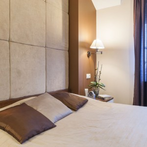 Ścianę nad łóżkiem w sypialni małżeńskiej wykończono miękkimi, szarymi płytami, które kreują przytulny klimat w pomieszczeniu. Projekt i zdjęcia: Gabinet Wnętrz.