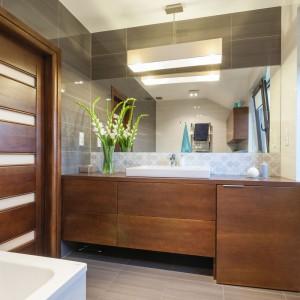 W łazience postawiono na podobną paletę barw, jak w salonie i kuchni. Odnajdziemy tutaj beże, brązy i szarości (choć z nie spotykaną w przestrzeni dziennej przewagą tych ostatnich). Obecność drewna nadaje wnętrzu charakter salonu kąpielowego. Projekt i zdjęcia: Gabinet Wnętrz.