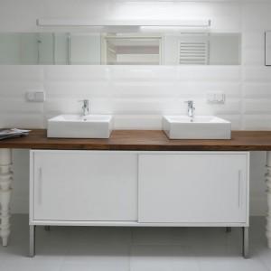 Białe płytki, które wyglądają jak starodawne kafle świetnie korespondują z prostą w formie szafką z ozdobnymi nóżkami. Dzięki bieli łazienka wydaje się wręcz sterylna, ale tę surowość przełamuje drewniany blat, który ociepla wnętrze. Projekt: Konrad Grodziński. Fot. Bartosz Jarosz.