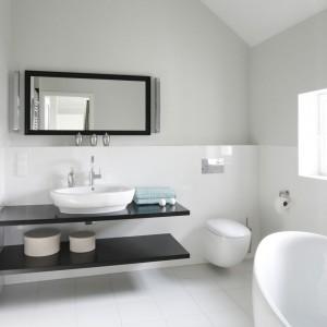 Prosta stylistyka łazienki została oparta na monochromie - bielą podkreślono opływowe miękkie kształty, zaś przedmioty o ostrych liniach dla kontrastu wyeksponowano czernią. Projekt: dom pokazowy na osiedlu Ventana. Fot. Bartosz Jarosz.