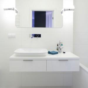 Tutaj wszystko jest białe: od ścian, podłogi i szafki, po umywalkę i wannę, dzięki temu wnętrze wydaje się niezwykle sterylne i chłodne. Jednak wystarczy wzbogacić je kolorowymi dodatkami, by nabrało charakteru. Projekt: Maciejka Peszyńska-Drews. Fot. Bartosz Jarosz.