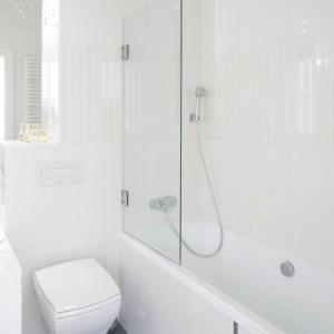 W tej łazience jedynym kontrastującym z wszechobecną bielą elementem jest ciemna podłoga. Warto podkreślić obecność praktycznego parawanu wannowego, dzięki któremu wanna może zamienić się w prysznic. Projekt: Kamila Paszkiewicz. Fot. Bartosz Jarosz.