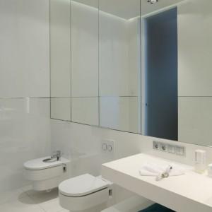 Przestrzeń dodatkowo rozświetlają i powiększają lustrzane fronty górnych szafek, poprowadzonych wzdłuż niemal całej ściany. Akcentem wprowadzającym do wnętrza kolor są błękitne drzwi. Projekt: Anna Maria Sokołowska. Fot. Bartosz Jarosz.