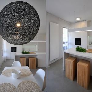 Salon, jadalnia i kuchnia stanowią wspólną przestrzeń dzienną, w której dominuje biel. Projekt: TK Architekci. Fot. Wojciech Szwej, Jose Teixeira.