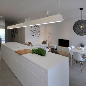 Wyspa wraz z dekoracyjną lampą oddzielają kuchnię od jadalni i salonu. Projekt: TK Architekci. Fot. Wojciech Szwej, Jose Teixeira.