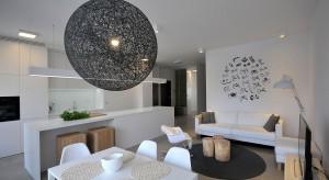W tym mieszkaniu króluje biel. Białe są ściany, meble i dodatki. Surowość, przełamana odrobiną szarości, czerni i drewna, tworzy niepowtarzalne wnętrze.