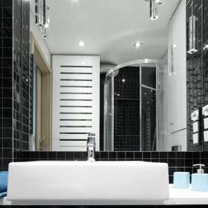 Strefa prysznica w całości została wykończona na czarno. W towarzystwie białych ścian drobne czarne płytki wyglądają nowocześnie - i pomimo ciemnego koloru - niezwykle lekko. Projekt: Marta Kilan. Fot. Bartosz Jarosz.