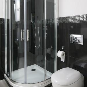 Czerń i biel to klasyczny duet, który świetnie pasuje do nowoczesnych aranżacji. W tej łazience czerń została złagodzona bielą ścian i podłogi oraz miękkimi, opływowymi kształtami miski wc, brodzika i kabiny prysznicowej. Projekt: Katarzyna Merta-Korzniakow. Fot. Bartosz Jarosz.