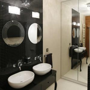 W tej łazience strefa umywalek została podkreślona elegancką oprawą. Ścianę nad stylową szafką wykończono szklaną mozaiką, zaś koliste lutra są efektownym uzupełnieniem. Projekt: Michał Mikołajczak. Fot. Bartosza Jarosz.