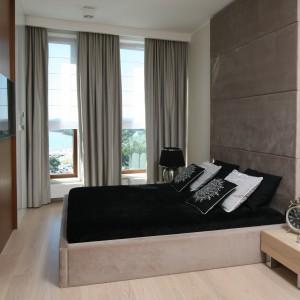 Tapicerowana ściana za łóżkiem w kolorze kawy z mlekiem sprawia wrażenie całości z łóżkiem obitym bardzo podobną tkaniną. Elegancki charakter aranżacji podkreślają ciężkie zasłony. Projekt: Anna Maria Sokołowska. Fot. Bartosz Jarosz.