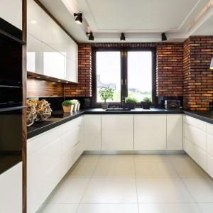 Do białych mebli i czarnych blatów pasują dodatki w różnych stylach. Może to być np. cegła na ścianie, tak jak w tej softloftowej kuchni. Nowoczesne, połyskujące fronty wieńczy czarny blat, harmonizujący z technicznymi lampami nad nim. Fot. Pracownia Mebli Vigo, kuchnia Brick.