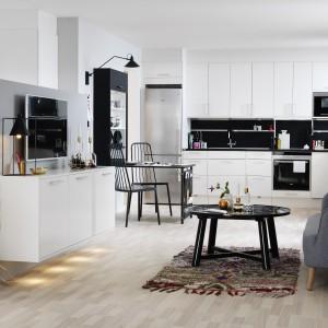 Jednorzędowa zabudowa utrzymana w nowoczesnej stylistyce i przewadze bieli, zaakcentowanej mocną czernią. Kolor ten jest obecny nie tylko na blacie kuchennym, ale i na ścianie nad nim. Fot. Marbodal, kuchnia Arkitekt Plus Vit.