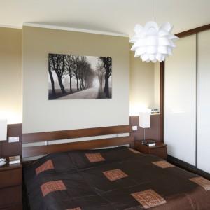 Ciepłą sypialnię bazującą na drewnie oświetla lampa sufitowa z IKEI o subtelnej formie przypominającej kwiat. Dla kontrastu, na stolikach nocnych ustawiono lampki o kubistycznym kształcie. Projekt: Piotr Stanisz. Fot. Bartosz Jarosz.