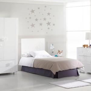 Biel to kolor, który dobrze wygląda we wnętrzach dla dorosłych oraz dzieci. Dla przełamania aranżacji wykorzystano ciemniejszą pościel w stonowanej kolorystyce. Gwiazdki na ścianie nad łóżkiem zdobią pokój oraz wyznaczają strefę snu. Fot. Micuna.